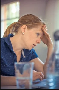 Annoyed Woman sitting with hand on forehead