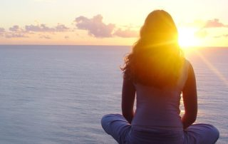 Woman sitting looking at sunset